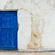 Old house white wall with blue door — Stock Photo #13548949