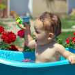 Cute funny baby boy bathing outdoor on green lawn among flowers — Stock Photo #13549119