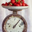 Retro scales with a handful of fresh ripe strawberries — ストック写真