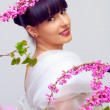 Beautiful smiling woman among pink flowers — Stock Photo