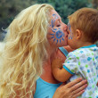 Face-painted mother kissing her little child — Stock Photo #13549231