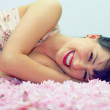 Beautiful smiling woman lying in flower petals — Stock Photo