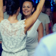 Group of fashionable positive girls dancing energetically in night club - Stok fotoğraf