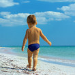 Small baby boy walking the seaside. rear view — Stock Photo