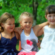 Three beautiful small girls friends embracing in green summer pa — Stock Photo