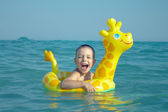 Happy laughing boy enjoying swimming in sea with rubber ring giraffe — Stock Photo