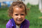 Poor and dirty, but still happy and smiling cute little gypsy girl — Stock Photo