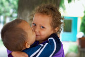 Cute small gypsy girl and boy kiss. outdoors — Stock Photo