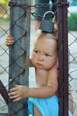 Locked baby boy trying to escape through wire fencing with padlo — Stock Photo