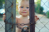 Upset baby boy looking out of locked wire fencing. outdoors — Stock Photo