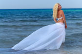 Attractive curly woman hovering over sea water, with white plume — Stock Photo
