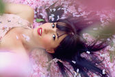 Beautiful woman lying in flower petals — Stock Photo