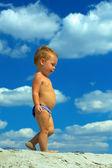 曇り空の背景のビーチの上を歩いてかわいい男の子。底面図 — ストック写真