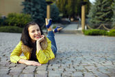 Beautiful happy woman lying on the ground — Stock Photo