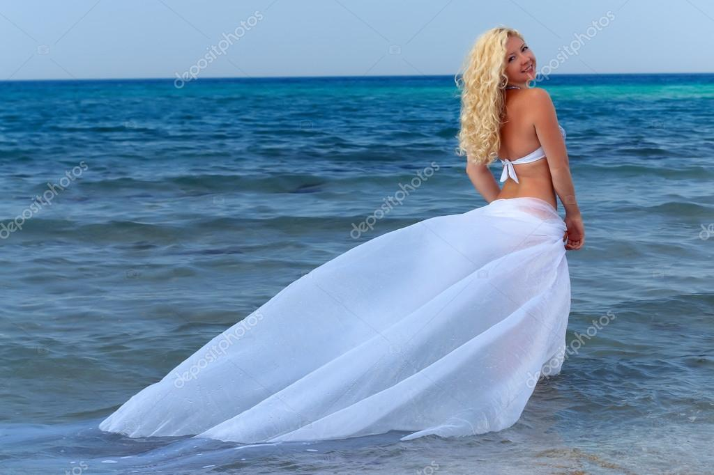Attractive curly woman hovering over sea water, with white plume  Stock Photo #13549080