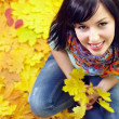 Happy smiling woman sitting in colorful fallen leaves — Photo