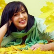 Attractive smiling brunette woman lying in yellow fallen leaves, wearing green scarf — Stock Photo #13550352