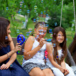 Three beautiful teenage girls having fun blowing bubbles in summ — Stock Photo #13550409