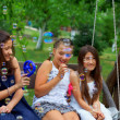Three beautiful teenage girls having fun blowing bubbles in summ — Stock Photo #13550417