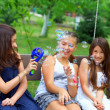 Three beautiful teenage girls having fun blowing bubbles in summ — Stock Photo