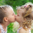 Two beautiful sisters kissing in summer park — Stock Photo