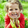 Little girl lying on grass at summer field. a bit dirty hands — Stockfoto