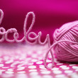 Baby word made of yarn among pink textile — Stock Photo #13550725