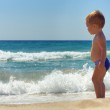 Cute baby boy standing in waves on the beach — Stock Photo