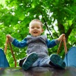 Small baby boy having fun on children's slide in spring park - Stock Photo