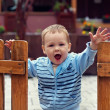 Cute boy stands in an open wooden fence with a welcome expressio — Stock Photo