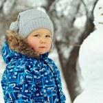 portrét krásného chlapečka s sněhulák venkovní v zimě — Stock fotografie