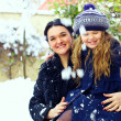 Beautiful mother and daughter smiling outdoor. winter snow — Stock Photo