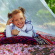 Cute little girl lying in summer arbor among pink petals — Stock Photo