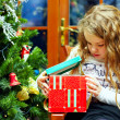 Beautiful little girl opens a gift box, christmas interior — Stock Photo