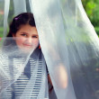 Cute little girl hiding face behind transparent tissue in summer — Stock Photo