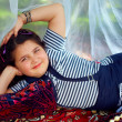 Cute little girl lying in turkish style arbor at summer garden — Stock Photo