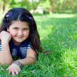 Beautiful little girl lying on green grass at summer field — Stock Photo #13551125