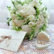 Wedding bouquet, rings and card on lace tablecloth — Stock Photo