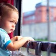 Cute little boy picking out from train window outside, while it moving — Stock Photo