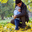 Happy father hugging little son in autumn park among fallen leaves — Stock Photo #13551443