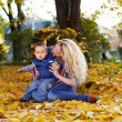 Attractive curly mother and son sitting on the carpet of fallen leaves in a — Stock Photo