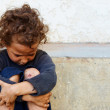 Poor, sad little child girl sitting against the concrete wall — Stock Photo #13551523