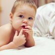 Curious little baby boy lying in bed at home — Stock Photo