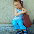 Cute baby boy with guitar sitting against the concrete wall — Lizenzfreies Foto