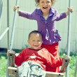 Poor but happy little gypsy siblings in swing outdoor — Stock Photo #13551555