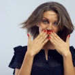 Close-up portrait of a surprised young girl hiding her mouth with hands — Stock Photo
