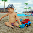 Cute baby boy playing with toys on beach — Stock Photo #13551689