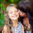 Beautiful mother kisses cute little daughter. outside in summer — Stock Photo