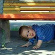 Funny mischievous baby boy peeking out from under the bench. outdoors — Stock Photo