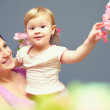 Stock Photo: Happy smiling mother with cute baby girl on hands among flowers